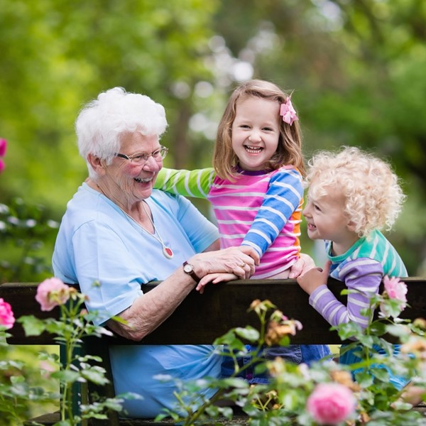 A grandparent laughs with her two grandchildren